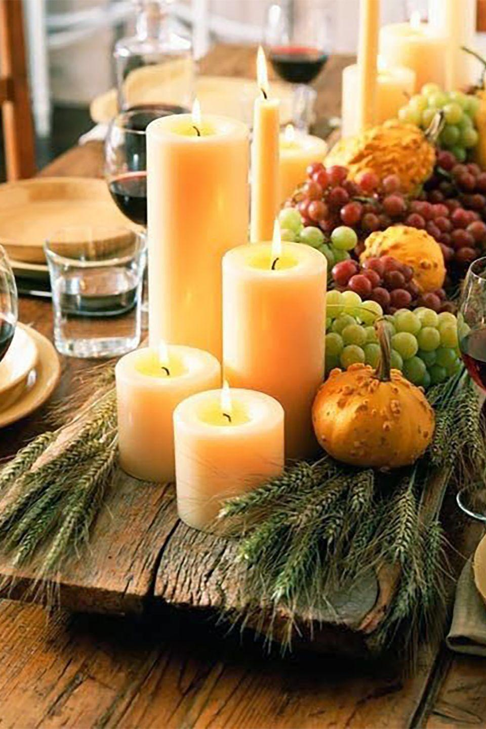 """<p>Arrange a large group of scentless white pillar candles in various heights on a large wooden tray in the center of your dining table. Add wheat stalks, fresh fruit, and gourds for an extra festive display.</p><p><a class=""""link rapid-noclick-resp"""" href=""""https://www.amazon.com/Bolsius-Pack-White-Pillar-Candles/dp/B004U3LZKM/ref=sr_1_9?tag=syn-yahoo-20&ascsubtag=%5Bartid%7C10050.g.1371%5Bsrc%7Cyahoo-us"""" rel=""""nofollow noopener"""" target=""""_blank"""" data-ylk=""""slk:SHOP CANDLES"""">SHOP CANDLES</a></p>"""