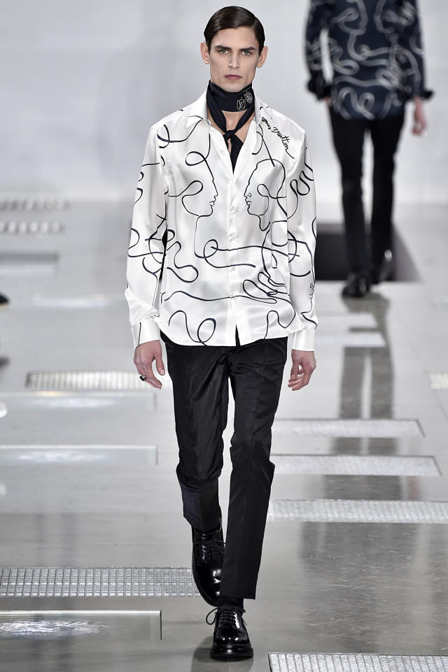 <p>Model wears a silk white shirt with Jean Cocteau-inspired illustrations, sleek black trousers, and a chic skinny neck scarf. (Photo: Getty Images) </p>