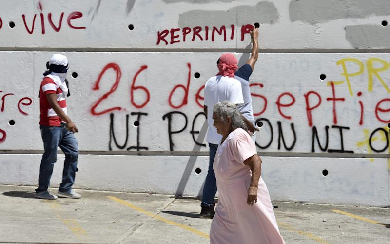 Students paint slogans on a wall as relatives and fellow students block the Chilpancingo-Acapulco highway during a protest to demand an explanation about missing students, in Chilpancingo, Guerrero state, Mexico on October 2, 2014 (AFP Photo/Yuri Cortez)