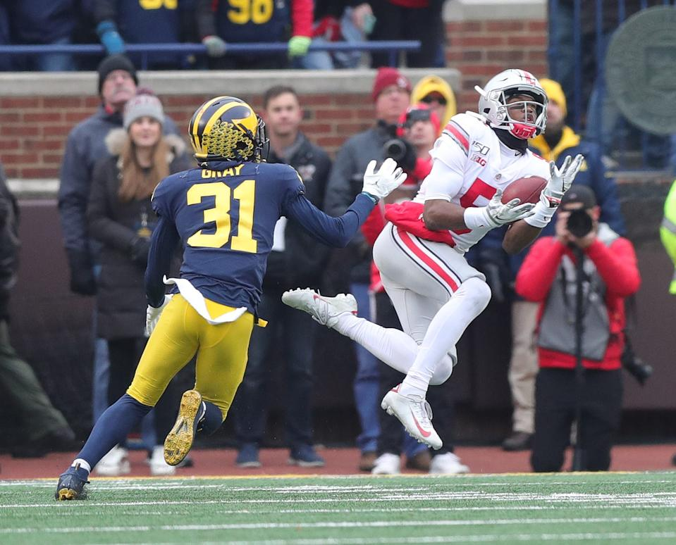 Ohio State receiver Garrett Wilson catches a long pass against Michigan defensive back Vincent Gray during the first half Saturday, Nov. 30, 2019, at Michigan Stadium.