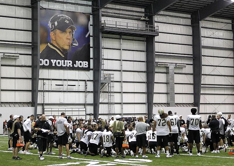 New Orleans Saints gather under a newly installed banner of suspended coach Sean Payton, at the conclusion of a day of NFL football training camp in Metairie, La., Friday, July 27, 2012. (AP Photo/Gerald Herbert)