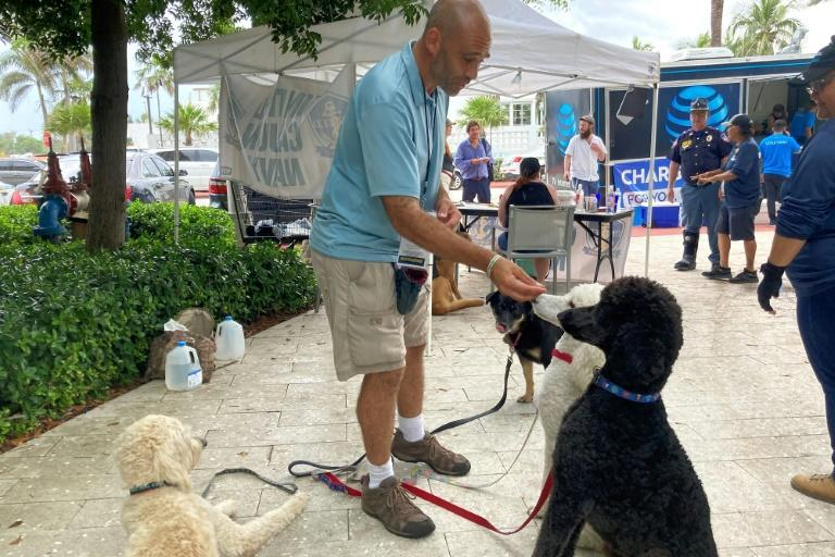 United Cajun Navy volunteer Jay Harris feeds dogs he brought for therapy in Surfside, Florida on June 28, 2021