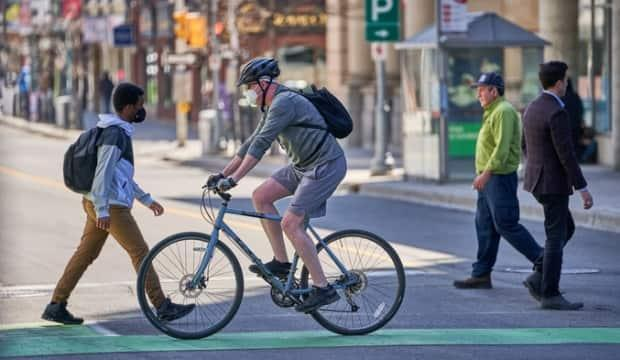 Pedestrians and a cyclist make their way through downtown Ottawa on April 7, 2021, during the COVID-19 pandemic. (David Richard/Radio-Canada - image credit)