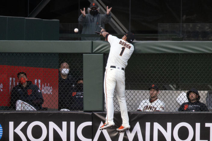 San Francisco Giants infielder Mauricio Dubón (1) leaps in vain for a two-run home run hit by Cincinnati Reds' Jesse Winker during the third inning of a baseball game, Monday, April 12, 2021, in San Francisco. (AP Photo/D. Ross Cameron)
