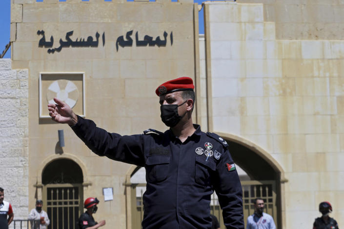 An officer stands guard outside Jordan's State Security Court where two former officials accused of helping Jordanian Prince Hamzah try to overthrow his half-brother King Abdullah II, await a verdict in their trial, in Amman, Jordan, Monday, July 12, 2021. The court sentenced the two to 15 years in prison. Bassem Awadallah, who has U.S. citizenship and once served as a top aide to King Abdullah II, and Sharif Hassan bin Zaid, a member of the royal family, were found guilty of sedition and incitement charges. (AP Photo/Raad Adayleh)
