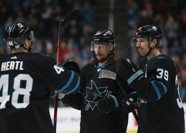 San Jose Sharks' Tomas Hertl (48) and Erik Karlsson (65) celebrate with Logan Couture (39), who scored a goal against the Vancouver Canucks during the first period of NHL hockey game in San Jose, Calif., Friday, Nov. 23, 2018. (AP Photo/Josie Lepe)