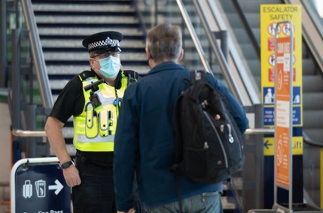 An officer from Avon and Somerset Police chats with a passenger at Bristol Airport