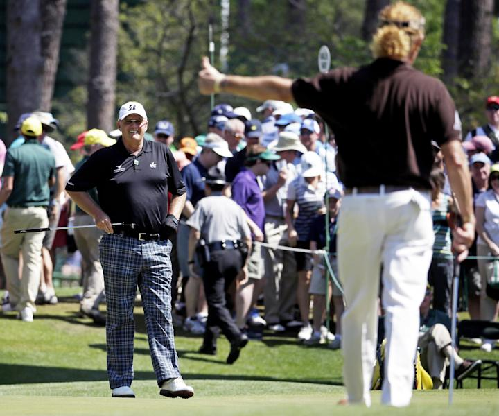 Miguel Angel Jimenez, right, of Spain, gives Sandy Lyle, of Scotland, a thumb's up after Lyle's birdie on the sixth green during the third round of the Masters golf tournament Saturday, April 12, 2014, in Augusta, Ga. (AP Photo/Darron Cummings)