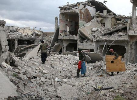 FILE PHOTO: People walk on rubble of damaged buildings in the besieged town of Douma