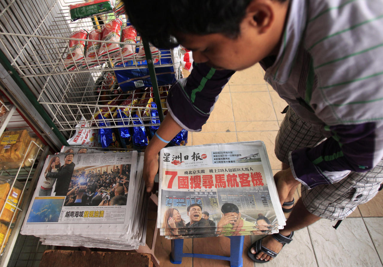 A vendor prepares newspapers carrying a headline story and pictures of Saturday's missing Malaysian Airlines plane, in Shah Alam, outside Kuala Lumpur, Malaysia, Sunday, March 9, 2014. An international fleet of planes and ships scouted the waters between Malaysia and Vietnam for any clues to the fate of the Malaysian Airlines Boeing 777, which disappeared less than an hour after taking off from Kuala Lumpur bound for Beijing. (AP Photo/Lai Seng Sin)