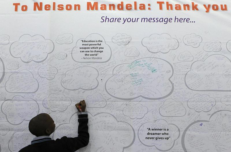 Thabiso Boya, adds his get-well message on a poster for former South African President Nelson Mandela, at the Education Expo in Johannesburg, South Africa Thursday, June 20, 2013. Mandela remains in the hospital for the 13th day. The 94-year-old was hospitalized for a recurring lung infection. (AP Photo/Themba Hadebe)