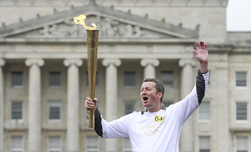 John McAlpine carries the Olympic torch at Parliament Buidings, Stormont, Belfast, Northern Ireland, Sunday, June 3, 2012, during its tour of Britain prior to the London 2012 games. (AP Photo/Peter Morrison)