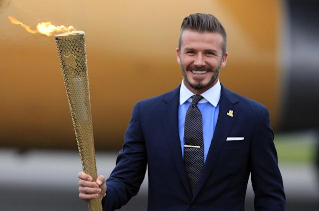 David Beckham holds the Olympic Flame as it arrives at RNAS Culdrose near Helston on May 18, 2012 in Cornwall, England. The Olympic Flame arrived in the UK after it was handed over at a ceremony yesterday in Athens. A British delegation including David Beckham, flew back with the flame from Greece where they attended a ceremony welcoming the flame, before it is taken on a 70-day relay involving 8,000 torchbearers covering 8,000 miles. (Photo by Matt Cardy/Getty Images)