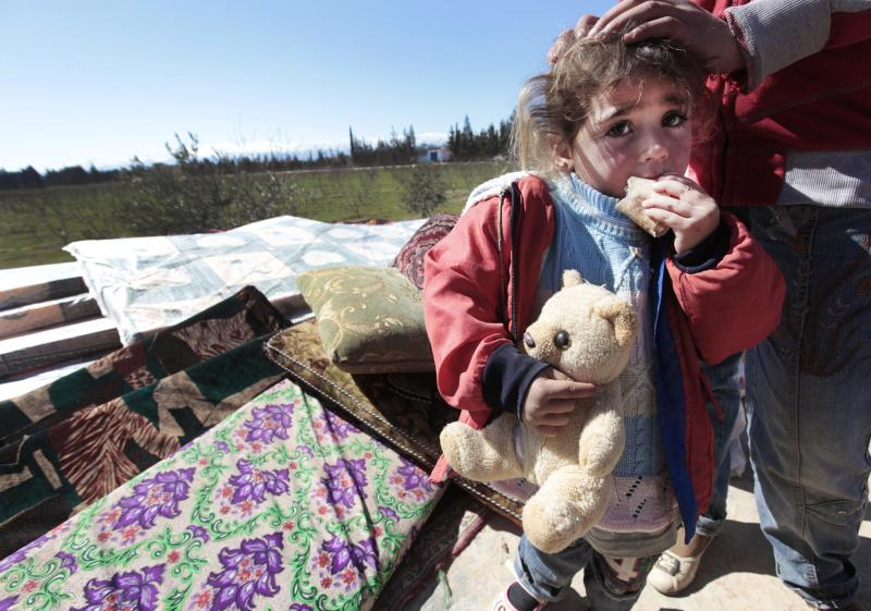 A Syrian child is seen with her family  who fled from the Syrian town of Qusair near Homs, at the Lebanese-Syrian border village of Qaa, eastern Lebanon,  Monday, March 5, 2012. More than a thousand Syrian refugees have poured across the border into Lebanon, among them families with small children carrying only plastic bags filled with their belongings as they fled a regime hunting down its opponents. (AP Photo/Hussein Malla)