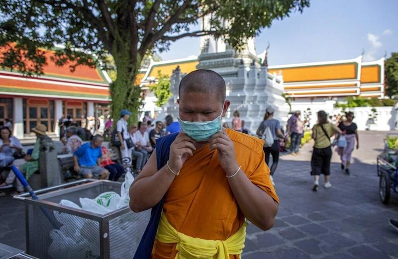 A Buddhist monk adjusts his face mask at the Wat Pho in Bangkok, Thailand. Image credit: AP