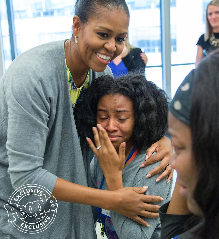 <p>Later on during the school visit, Michelle offers a hug to a student who is <em>very </em>happy to see her.</p>
