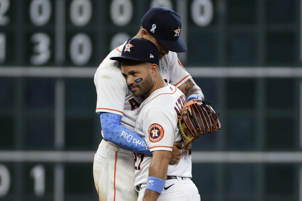 Houston Astros' Jose Altuve, bottom, and Carlos Correa, top, celebrate their win over the Chicago White Sox in a baseball game, Sunday, June 20, 2021, in Houston. (AP Photo/Eric Christian Smith)