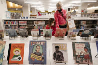 Zoe Slavin and her mother, Julie, browse for books in the children's section of the Stavros Niarchos Foundation Library, Tuesday, June 1, 2021 in New York. The city's central circulation library, closed for renovations in 2017, fully reopens today. It was previously called the Mid-Manhattan Library. (AP Photo/Mark Lennihan)