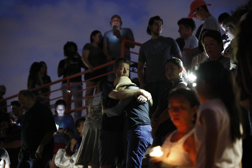 People embrace during a vigil for victims of the shooting Saturday, Aug. 3, 2019, in El Paso, Texas. A young gunman opened fire in an El Paso, Texas, shopping area during the busy back-to-school season, leaving multiple people dead and more than two dozen injured. (AP Photo/John Locher)