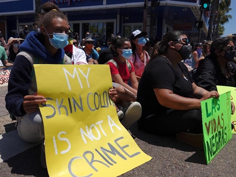 """A young woman holds a sign saying """"My Skin Color is not a Crime"""" during A Black Lives Matter protest rally, one of many in San Diego County, June 7, 2020."""