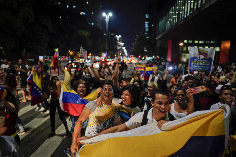 Venezuelan anti-government protesters hold their national flag as they block traffic during a demonstration in Sao Paulo, Brazil, Wednesday, Jan. 23, 2019. Venezuelan migrants held a rally against Venezuelan President Nicolas Maduro and in favor of Juan Guaido, head of Venezuela's opposition-run congress who today declared himself interim president of the South American nation. (AP Photo/Victor R. Caivano)