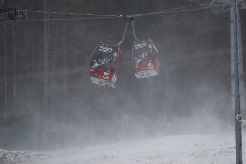 Cable cars are blown by strong winds during a pause of an alpine ski, women's World Cup giant slalom, in Semmering, Austria, Monday, Dec. 28, 2020. (AP Photo/Gabriele Facciotti)