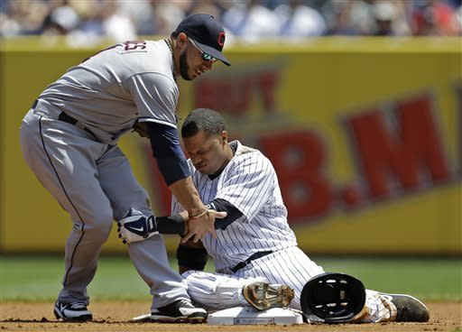 Cleveland Indians shortstop Mike Aviles, left, steadies New York Yankees Robinson Cano after Cano slid hard into second with a double in the first inning of a baseball game at Yankee Stadium in New York, Wednesday, June 5, 2013. Cano later scored on Travis Hafner's two-run home run. (AP Photo/Kathy Willens)