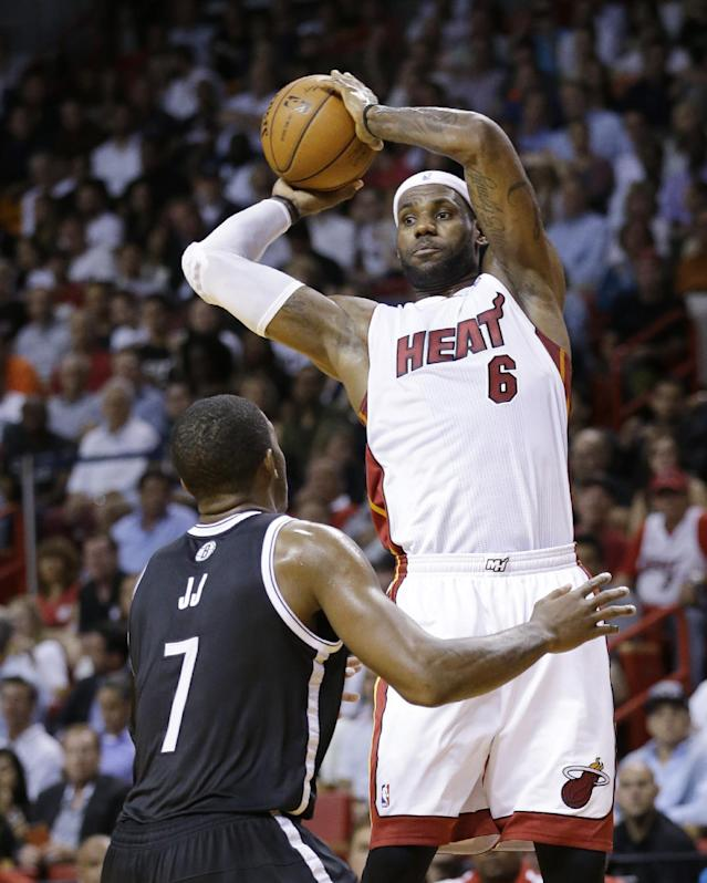 Miami Heat forward LeBron James (6) passes past Brooklyn Nets guard Joe Johnson (7) during the first half of an NBA basketball game, Tuesday, April 8, 2014 in Miami. (AP Photo/Wilfredo Lee)
