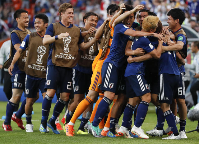 Japan players celebrate after their teammate Takashi Inui scored their side's first goal during the group H match between Japan and Senegal at the 2018 soccer World Cup at the Yekaterinburg Arena in Yekaterinburg , Russia, Sunday, June 24, 2018. (AP Photo/Natacha Pisarenko)