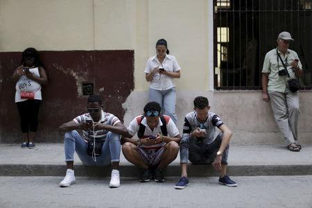 People sit and stand near a Wi-Fi hotspot in Havana, March 17, 2016. REUTERS/Ueslei Marcelino/Files