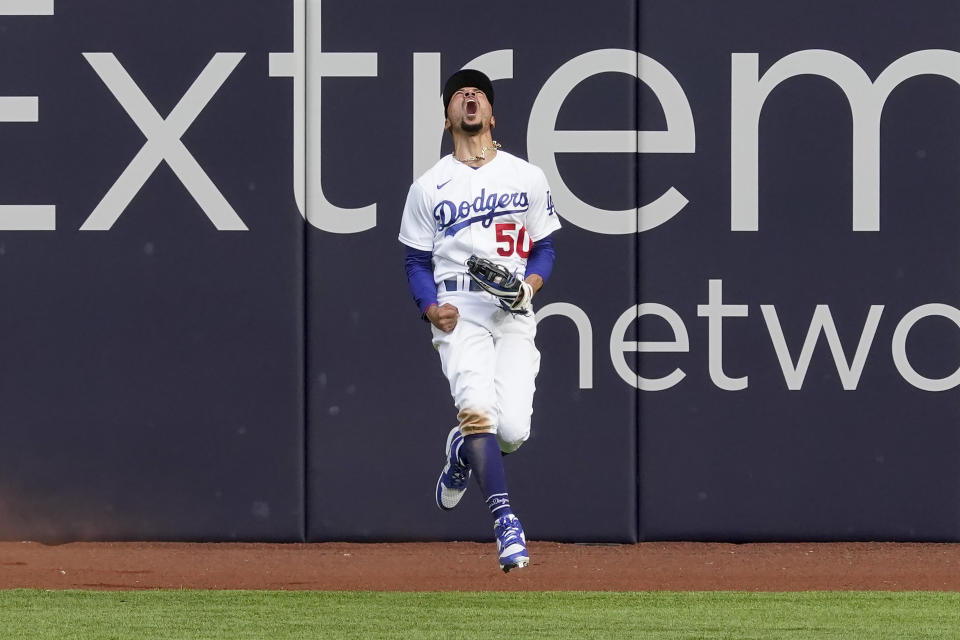 Los Angeles Dodgers right fielder Mookie Betts celebrates after robbing Atlanta Braves' Marcell Ozuna of a home during the fifth inning in Game 6 of a baseball National League Championship Series.