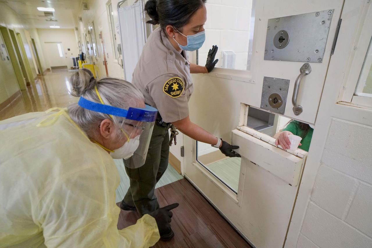 TOPSHOT - A Sheriff's deputy and on-site nurse give medications to an inmate at Las Colinas Women's Detention Facility in Santee, California, on  April 22, 2020. - Inmates and Sheriff's deputies at the prison are practicing COVID-19 measures including wearing masks, staying keeping a safe distance and doing more frequent cleaning at the facility. (Photo by Sandy Huffaker / AFP) (Photo by SANDY HUFFAKER/AFP via Getty Images)