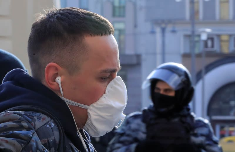 A man wearing a protective mask walks past a law enforcement officer in central Moscow