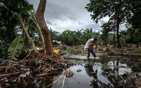 <span>A man walks through debris after hit by tsunami as they carry their belongings</span>
