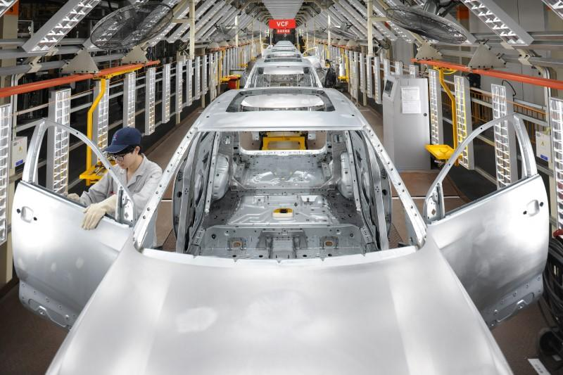 Employees work at a production line at a newly opened a Dongfeng Peugeot Citroen factory in Chengdu