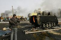 An Egyptian demonstrator uses his mobile phone to take a picture of a burnt army tank during clashes in central Cairo on January 29, 2011