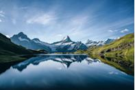 <p>Bright blue skies reflect on the waters of Bachalpsee Lake in Grindelwald, Switzerland.</p>