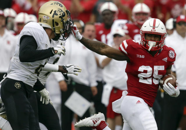 Nebraska running back Greg Bell (25) stiff-arms Colorado defensive backs Delrick Abrams Jr. (1) and Dante Wigley (4) during the first half of a game in 2018. (AP)