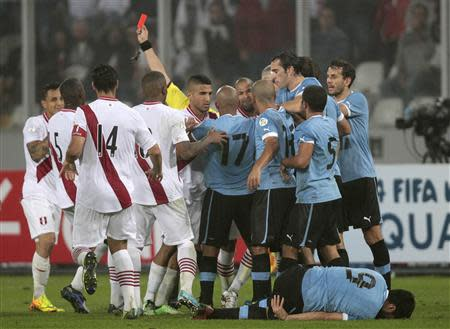 Peru and Uruguay players scuffle after the referee sends off Peru's Victor Yotun (not pictured) with a red card during their 2014 World Cup qualifying soccer match in Lima, September 6, 2013. REUTERS/Mariana Bazo