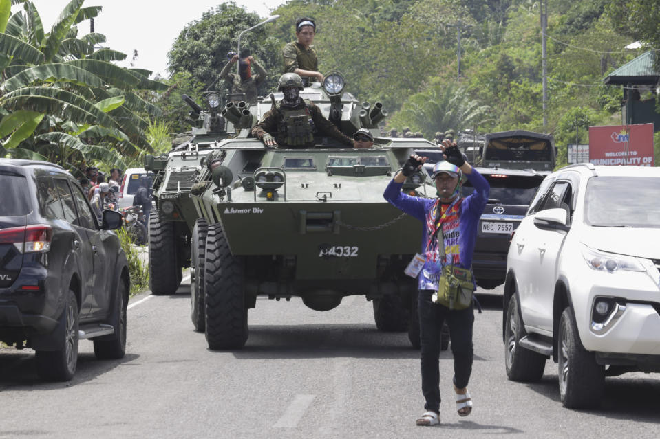 Armored personnel carriers make their way along traffic as they augment security forces in Datu Paglas, Maguindanao province, southern Philippines on Saturday May 8, 2021. Dozens of Muslim militants occupied a public market overnight in the southern Philippines before fleeing after a tense standoff with government forces, officials said Saturday. (AP Photo/Ferdinandh Cabrera)