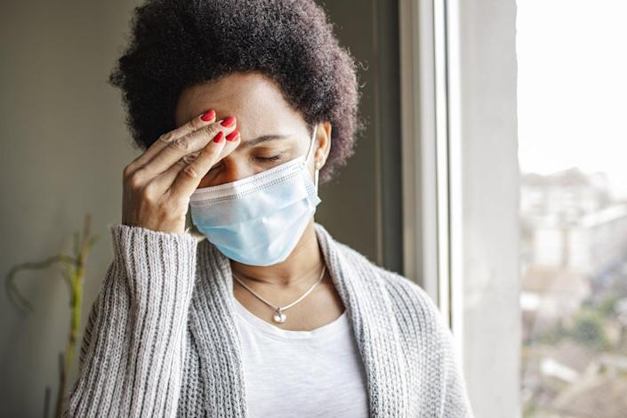 African American woman looking stressed and wearing a face mask near a window.