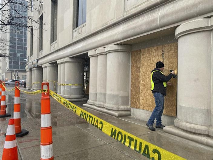 A worker boards up the George Romney State Office Building in Lansing, Mich., and yellow caution tape surrounds it.