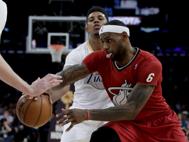 Miami Heat forward LeBron James, right, drives past Los Angeles Lakers forward Nick Young during the second half of an NBA basketball game in Los Angeles, Wednesday, Dec. 25, 2013. The Heat won 101-95. (AP Photo/Chris Carlson)