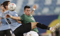 Uruguay's Rodrigo Bentancur, left, fights for the ball with Bolivia's Henry Vaca during a Copa America soccer match at Arena Pantanal in Cuiaba, Brazil, Thursday, June 24, 2021. (AP Photo/Andre Penner)