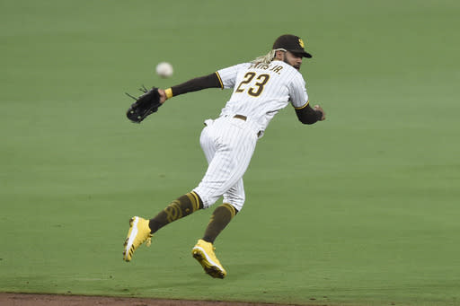 San Diego Padres shortstop Fernando Tatis Jr. throws to first base on a single hit by Seattle Mariners' Evan White during the third inning of a baseball game Friday, Sept. 18, 2020, in San Diego. White was safe at first base. (AP Photo/Denis Poroy)