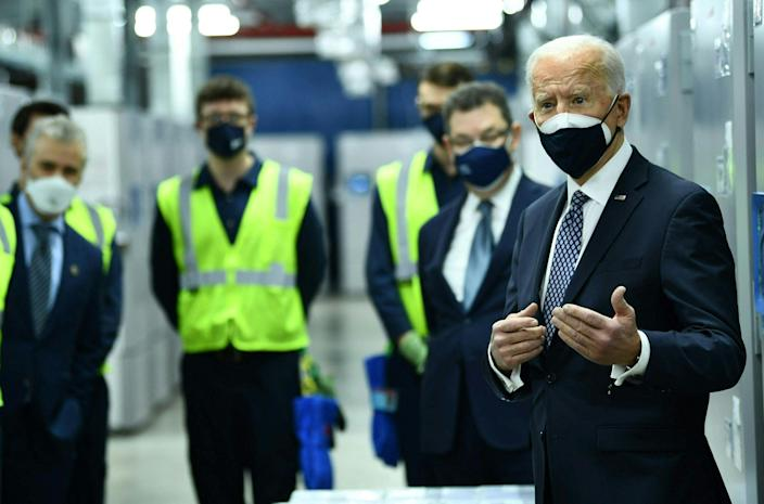 President Joe Biden speaks with workers at a Pfizer facility in Michigan on 19 February. (AFP via Getty Images)