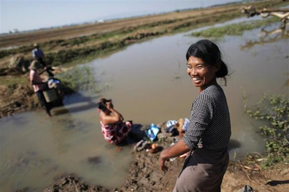 Women wash clothes and bath at a river in the outskirts of capital Naypyitaw, January 24, 2012.