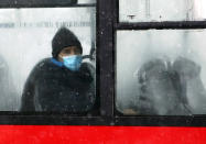 A man wearing a face mask to protect against coronavirus looks out from a bus in Belgrade, Serbia, Monday, Jan. 11, 2021. A spate of rainy and snowy weather across the Balkans in the past days has left homes and fields flooded, disrupted road and sea traffic and caused power outages. (AP Photo/Darko Vojinovic)