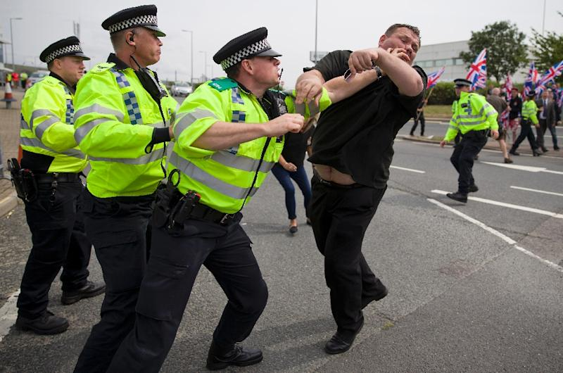 Police clash with nationalist counter demonstrators as people rally to support migrants trying to cross into England through the channel tunnel from France, near an entrance to the Eurotunnel terminal in Folkestone, on August 1, 2015 (AFP Photo/Justin Tallis)