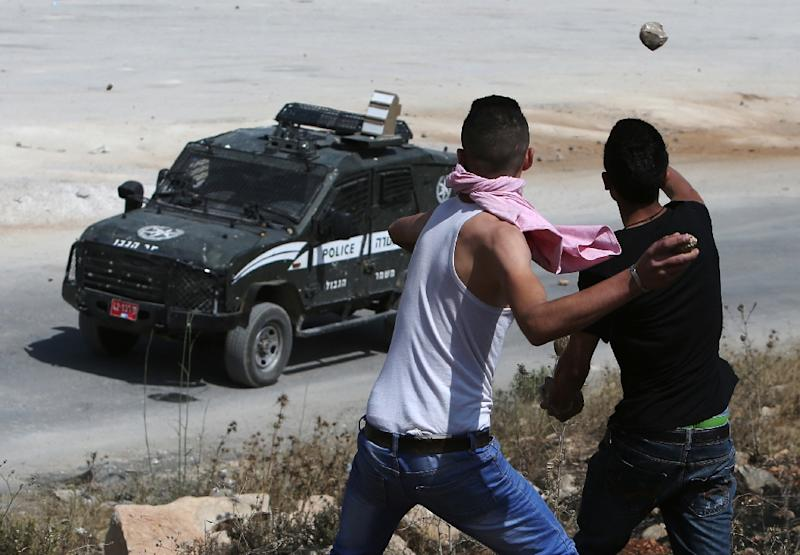 Palestinian protesters throw stones towards Israeli security forces during clashes near the West Bank town of Betunia on June 12, 2015 (AFP Photo/Abbas Momani)